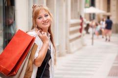 Szczęśliwa dziewczyna chodzi przez ulicy po robić zakupy Ona mienie obrazy stock