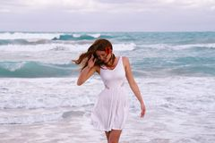 Szczęśliwa dziewczyna chodzi wzdłuż plaży blisko oceanu fotografia royalty free