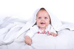 Szczęśliwa dziewczyna chuje w łóżku pod białym coverlet lub koc Dziewczyna przy łóżkiem łóżkowy dziecko Na białym tle zdjęcia royalty free