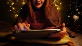 Szczęśliwa dziewczyna cieszy się ogólnospołeczne sieci na pastylce Zdjęcia Stock