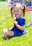 Szczęśliwa dziewczyna cieszy się Popsicle na 4th Lipiec Zdjęcie Royalty Free