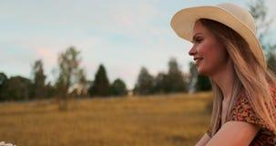 Szczęśliwa dziewczyna jedzie rower w kapeluszu i lato skrótu sukni z bukietem kwiaty zbiory