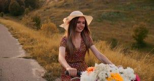 Szczęśliwa dziewczyna jedzie rower w kapeluszu i lato skrótu sukni z bukietem kwiaty zdjęcie wideo