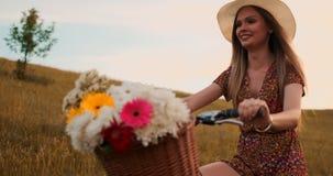 Szczęśliwa dziewczyna jedzie rower w kapeluszu i lato skrótu sukni z bukietem kwiaty zbiory wideo