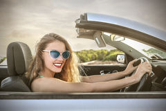 Szczęśliwa dziewczyna jedzie samochód Zdjęcia Stock