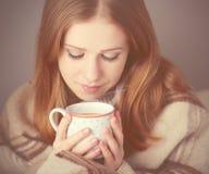 Szczęśliwa dziewczyna jest pod filiżanką kawy na zima ranku i koc w domu Zdjęcia Royalty Free