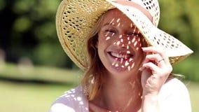 Szczęśliwa dziewczyna jest ubranym słomianego kapelusz ono uśmiecha się przy kamerą zdjęcie wideo