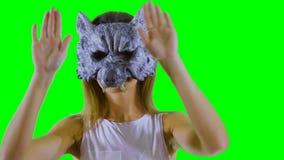 Szczęśliwa dziewczyna jest ubranym wilk maskę tanczy przy zielonym tłem i pokazuje aprobaty zbiory