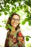 Szczęśliwa dziewczyna między drzewnymi liśćmi fotografia royalty free