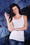 Szczęśliwa dziewczyna na drelichowym tle fotografia stock