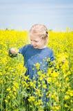 Szczęśliwa dziewczyna na kwitnącym rapeseed polu w lecie Obrazy Stock