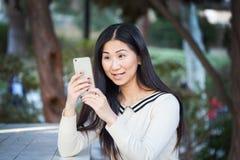 Szczęśliwa dziewczyna ono wpatruje się na jej telefonie z zachwytem Zdjęcia Stock