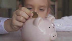 Szczęśliwa dziewczyna oprócz pieniądze w prosiątko banku w ona do domu Dziecko wkłada monetę w prosiątko banka, salowy pieniężny  zdjęcie wideo
