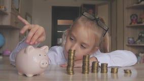 Szczęśliwa dziewczyna oprócz pieniądze w prosiątko banku w ona do domu Dziecko wkłada monetę w prosiątko banka, salowy pieniężny  zbiory wideo