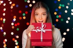 Szczęśliwa dziewczyna otwiera Bożenarodzeniowego pudełko który jest rozjarzonym inside Bożenarodzeniowy prezent Zdjęcie Stock
