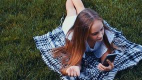 Szczęśliwa dziewczyna pisać na maszynie sms telefonem kłama na trawie w parku Kolor Oceniać zdjęcie wideo