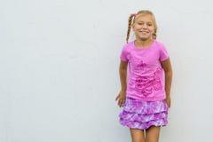 Szczęśliwa dziewczyna przed ścianą Zdjęcia Stock