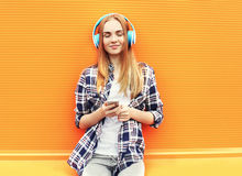 Szczęśliwa dziewczyna słucha dobrą muzykę w hełmofonach i cieszy się zdjęcie stock