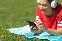 Szczęśliwa dziewczyna słucha muzyczna wyszukuje telefon zawartość na trawie zdjęcia royalty free