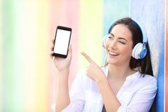 Szczęśliwa dziewczyna słucha muzyka pokazuje i punkty dzwonią ekran fotografia royalty free