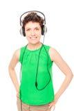 Szczęśliwa dziewczyna słucha twój ulubiona muzyka z hełmofonami na bielu obraz stock