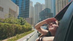 Szczęśliwa dziewczyna siedzi na tylnym siedzeniu samochód i podróżuje wokoło miasta Dubaj obraz royalty free