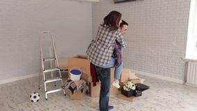 Szczęśliwa dziewczyna skacze z tyłu jej rozochoconego faceta w nowym mieszkaniu nowy dom zbiory wideo