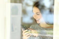 Szczęśliwa dziewczyna sprawdza mądrze telefon zawartość na linii zdjęcia stock