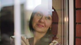 Szczęśliwa dziewczyna trzyma filiżanki kawy obsiadanie na windowsill w piżamach zdjęcie wideo