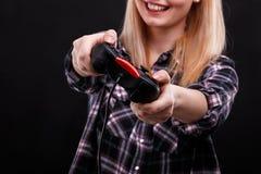 Szczęśliwa dziewczyna trzyma gemowych ono uśmiecha się i joystick Na czarnym tle Obrazy Stock