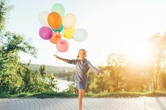 Szczęśliwa dziewczyna trzyma kolorowych balony w miasto parku, bawić się a obraz stock