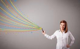 Szczęśliwa dziewczyna trzyma telefon z kolorowymi abstrakcjonistycznymi liniami Obrazy Stock