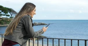 Szczęśliwa dziewczyna używa mądrze telefon w balkonie