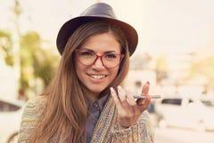 Szczęśliwa dziewczyna używa mądrze telefonu głosu rozpoznania funkcję na kreskowym odprowadzeniu na ulicie zdjęcia stock