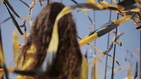 Szczęśliwa dziewczyna w żółty hoody w okulary przeciwsłoneczni podwyżki rękach wśród falowanie taśm Lato wietrzny dzień festiwale zdjęcie wideo