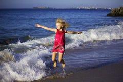 Szczęśliwa dziewczyna w barwionym smokingowym doskakiwaniu na falach na plaży fotografia stock