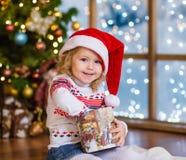 Szczęśliwa dziewczyna w czerwonych Santa otwarcia bożych narodzeń kapeluszowych prezentach Fotografia Royalty Free