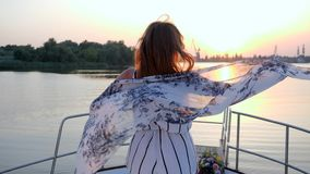 Szczęśliwa dziewczyna w falowanie ubiór meandrować pozycję na pokładzie na jachcie w morzu na tle zmierzchu above - woda zdjęcie wideo