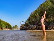 Szczęśliwa dziewczyna w jaskrawym bikini stojaku w dennej lagunie fotografia stock