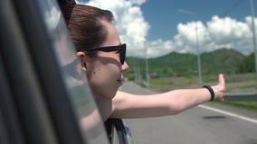 Szczęśliwa dziewczyna w okularach przeciwsłonecznych opiera z samochodowego okno i cieszy się wycieczkę w górach Młodej kobiety p zbiory
