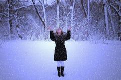 Szczęśliwa dziewczyna w opadzie śniegu chodzi w wieczór parku, raduje się, ono uśmiecha się, obraz royalty free