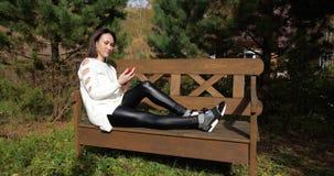Szczęśliwa dziewczyna w Parkowym obsiadaniu na ławce, młoda kobieta, z telefonem, długi brunetka włosy zdjęcie wideo
