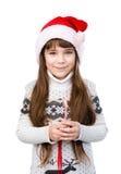 Szczęśliwa dziewczyna w Santa kapeluszu z Bożenarodzeniową cukierek trzciną Odizolowywający na bielu zdjęcie royalty free