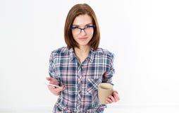 Szczęśliwa dziewczyna w szkłach z filiżanką gorącego napoju pisać na maszynie sms na białym tle zdjęcia stock