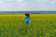 Szczęśliwa dziewczyna z długie włosy bieg przez żółtego kwiatu pole W?osy rozwija fotografia stock