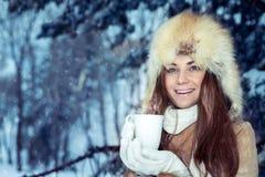 Szczęśliwa dziewczyna z filiżanką herbata w zima parku fotografia stock