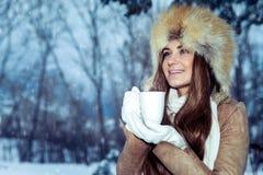 Szczęśliwa dziewczyna z filiżanką herbata w zima parku obrazy stock