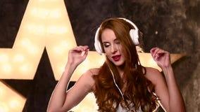 Szczęśliwa dziewczyna z hełmofonami w muzycznym studiu, wolnym zbiory wideo