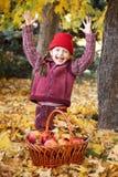 Szczęśliwa dziewczyna z jabłczanym koszem w jesieni lasowy pozować, kolorów żółtych liściach i drzewach na tle, Zdjęcia Stock