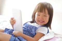 Szczęśliwa dziewczyna z pastylka komputerem osobistym Fotografia Stock
